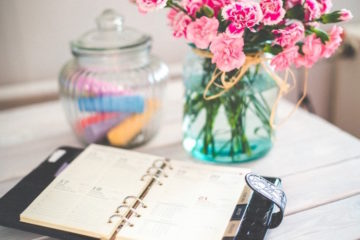 personal-organizer-and-bunch-of-pink-flowers-in-vase-on-desk
