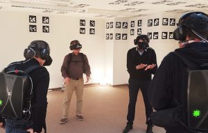 Four participants look around the virtual world in Illusion Walk's Immersion Deck.