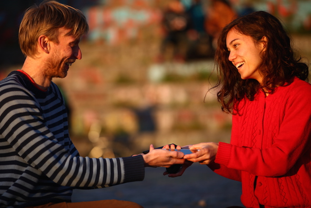 A man and a woman meet to trade items after connecting on Jaspr.